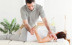 man carrying out physiotherapy on ladys shoulder